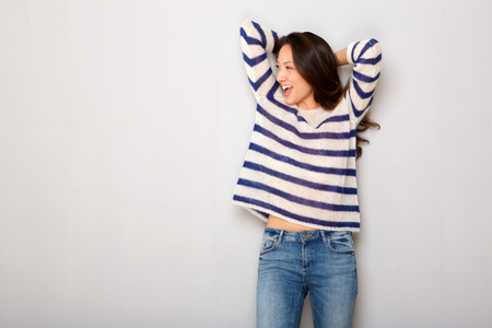 Portrait of happy attractive young asian woman laughing with hands behind head Stock Photo