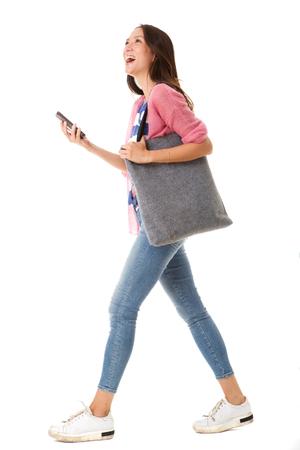 Retrato del lado del cuerpo completo de la mujer asiática joven de moda que camina con el bolso y el teléfono inteligente contra el fondo blanco aislado