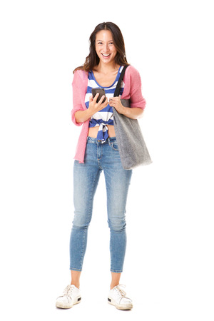 Full body portrait of trendy young asian woman standing against isolated white background with purse and mobile phone