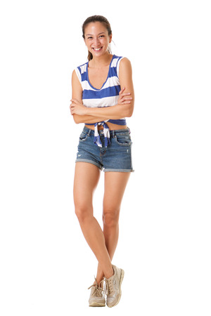 Full body portrait of beautiful young asian woman smiling shorts against isolated white background Stockfoto