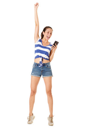 Full length portrait of happy young asian woman punching the air with mobile phone against white background