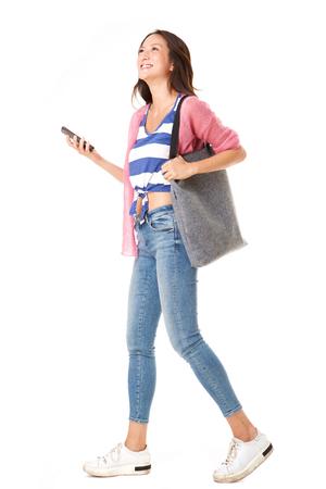 孤立した白い背景に対してハンドバッグと携帯電話で歩くファッショナブルな若いアジアの女性のフルボディサイドの肖像画