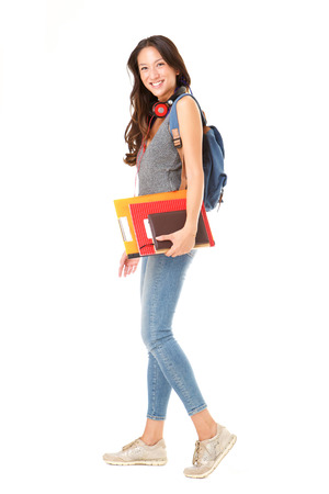 Full body side portrait of asian female college student walking against isolated white background with books and bag