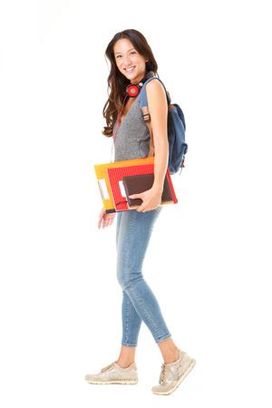 Portrait complet du corps d'une étudiante asiatique marchant sur un fond blanc isolé avec des livres et un sac
