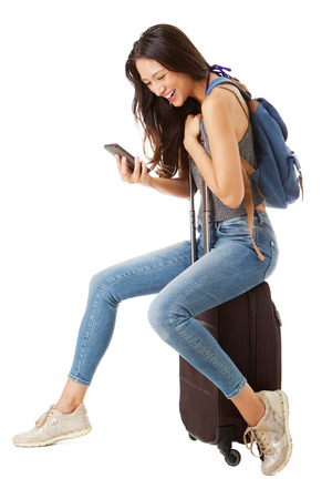 Full body side portrait of happy asian female traveler sitting on suitcase and looking at cellphone against isolated white background Фото со стока