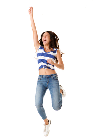 Full body portrait of joyful young asian woman jumping in the air against isolated white background