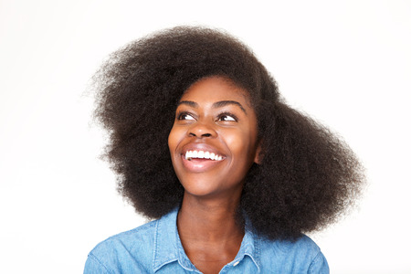 Close up portrait of young african american woman smiling and looking up Фото со стока