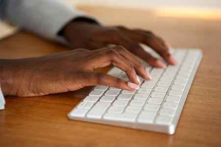 Close up african american female hands typing on computer keyboard