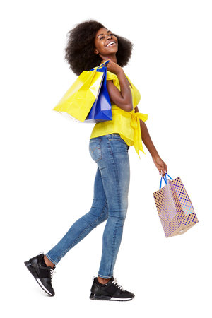 Full body side portrait of young black woman walking with shopping bags against isolated white background