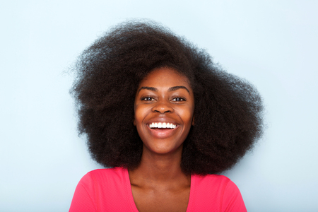 Close up portrait of happy young black woman against blue background
