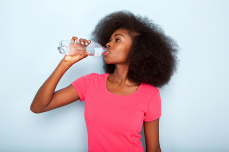 Close up portrait of young black woman drinking bottle of water 写真素材