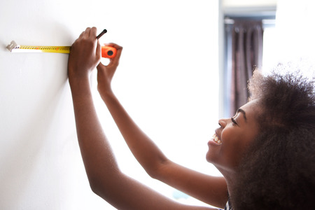 Close up portrait of happy young black woman measuring on wall