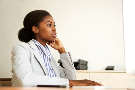 Portrait of serious young black business woman sitting in office looking at computer screen
