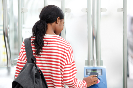 Behind of young black woman using ticket to go through turnstile at station Imagens
