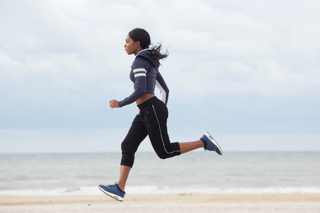 Full body side portrait of sporty young black woman running by the beach