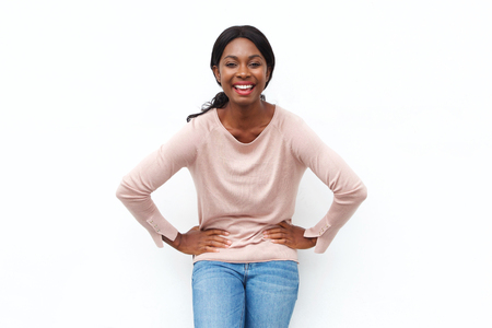 Portrait of happy young black woman laughing with hands on hips against isolated white background