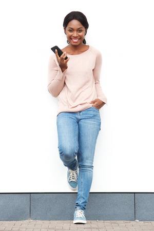 Full length portrait of smiling young black woman standing against white wall with cellphone Stock fotó