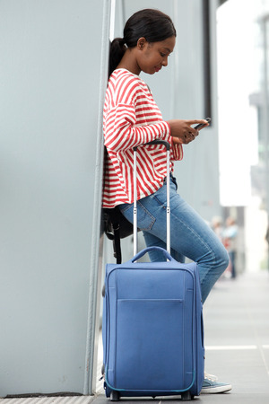 Full length side portrait of young woman traveling with suitcase in airport looking at cellphone