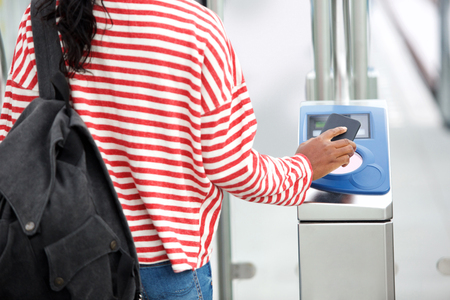 Close up female hand holding phone to open turnstile