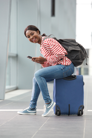 Portrait of happy young black woman sitting on suitcase with mobile phone at station 스톡 콘텐츠