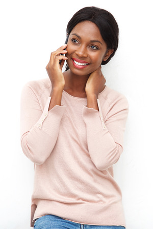 Portrait of attractive young black woman talking ion cellphone against isolated white background