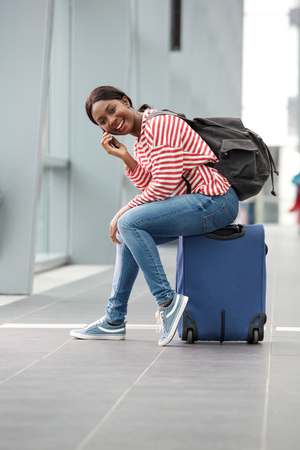 Portrait of cheerful young african american woman sitting on suitcase at station and talking on cellphone