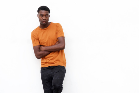 Portrait of serious young black man in t shirt posing against isolated white background with arms crossed
