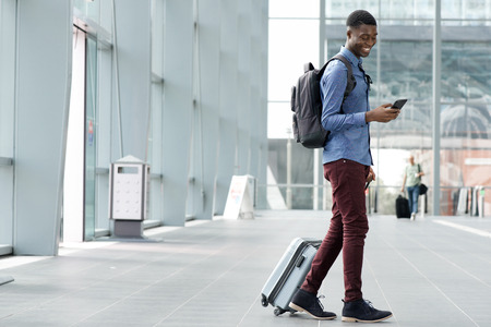 Full body side portrait of young black man traveling with suitcase and cellphone at airport 免版税图像
