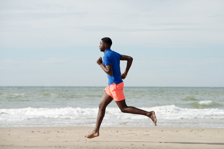 Full body side portrait of healthy african american man running at beach