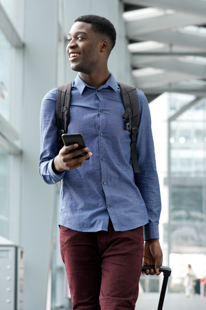 Portrait of smiling young black man traveling with bags and mobile phone Stock Photo