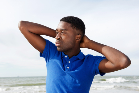 Close up portrait of cool young african american man with hands behind head at beach