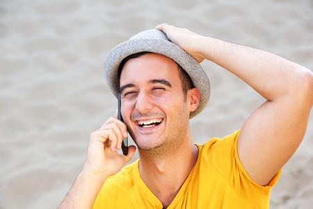 Close up portrait of happy man with hat talking on mobile phone at the beach