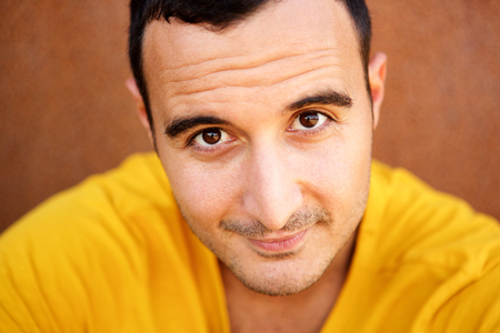 Close up portrait of latin man against brown background Stock Photo - 113221358