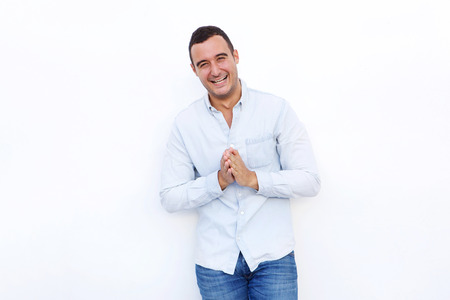 Portrait of attractive man laughing with hands clasp against isolated white background Foto de archivo - 113230024