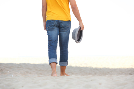 Low angle of man walking barefoot on sand at the beach Stockfoto