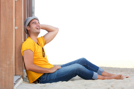 Side portrait of relaxed happy man sitting on sand at the beach with hat Stok Fotoğraf