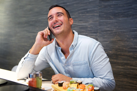 Portrait of happy man talking on mobile phone at sushi restaurant