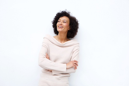 Portrait of middle age woman smiling with arms crossed against white background Stockfoto