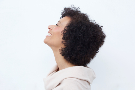 Close up profile portrait of woman laughing against white background