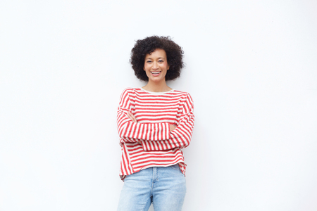 Portrait of happy african american woman smiling with arms crossed against white wall