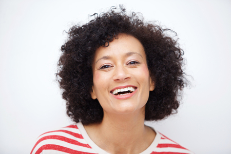 Close up front portrait of and older african american woman laughing against white background