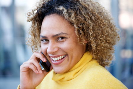 Close up portrait of happy african american woman with curly hair talking on mobile phone