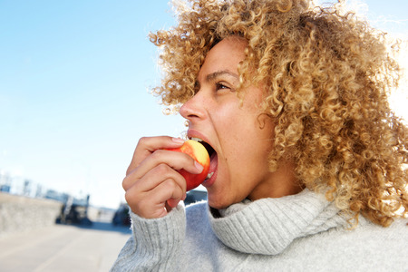 Close up side portrait of healthy young african american woman eating apple Imagens