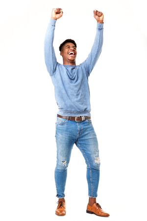Full body portrait of cheerful young black man with arms raised against isolated white background