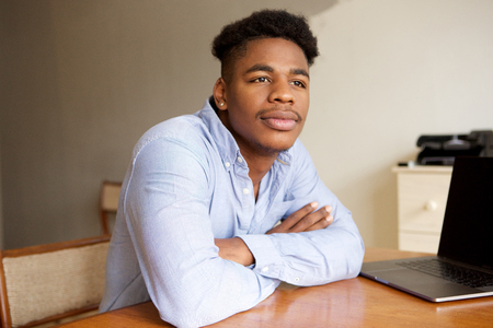 Close up portrait of young african american businessman daydreaming at desk ion office Stock Photo