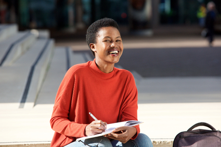 Portrait of happy young black woman writing in book outside
