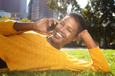 Close up portrait of happy young black woman smiling outdoors in park and talking with mobile phone