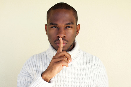 Close up portrait of handsome young african american man with finger over lips