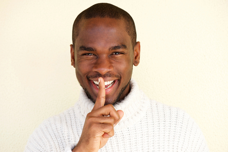 Close up portrait of smiling african american man with finger over lips 版權商用圖片