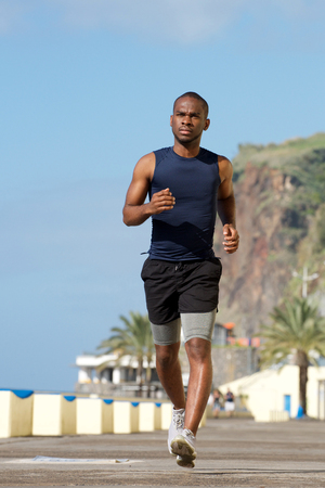 Full body portrait of healthy young african american man running outside